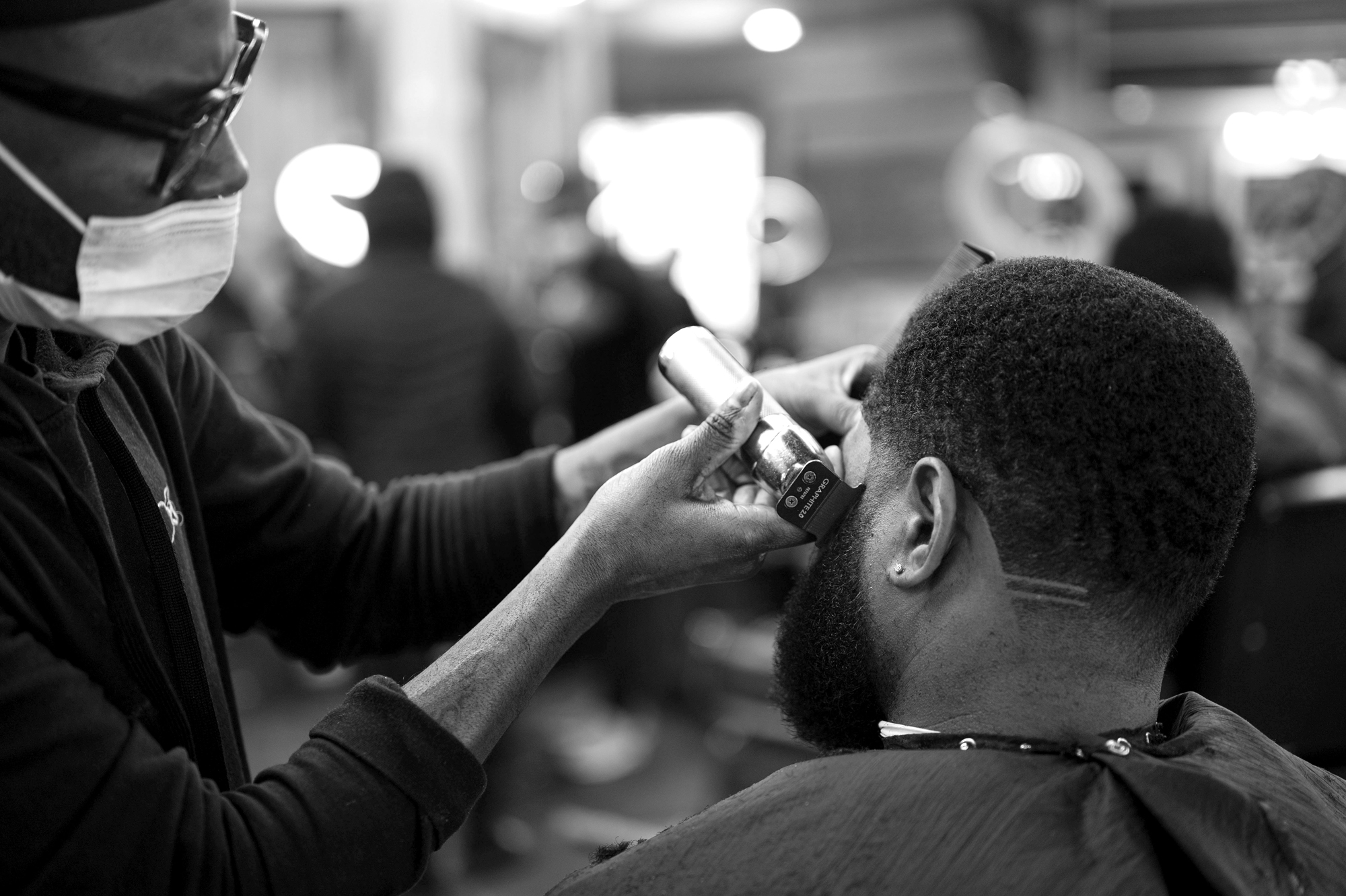 A black and white photo of one person using clippers to cut another person's hair. Both people are dark-skinned, and the person getting their hair cut has short hair and a beard. The back of their head is facing us, and they're wearing a black hair-cutting apron and a diamond earring in their left ear. The person cutting their hair is wearing a black, long-sleeved shirt and a white mask. Photo by Katie Sikora.