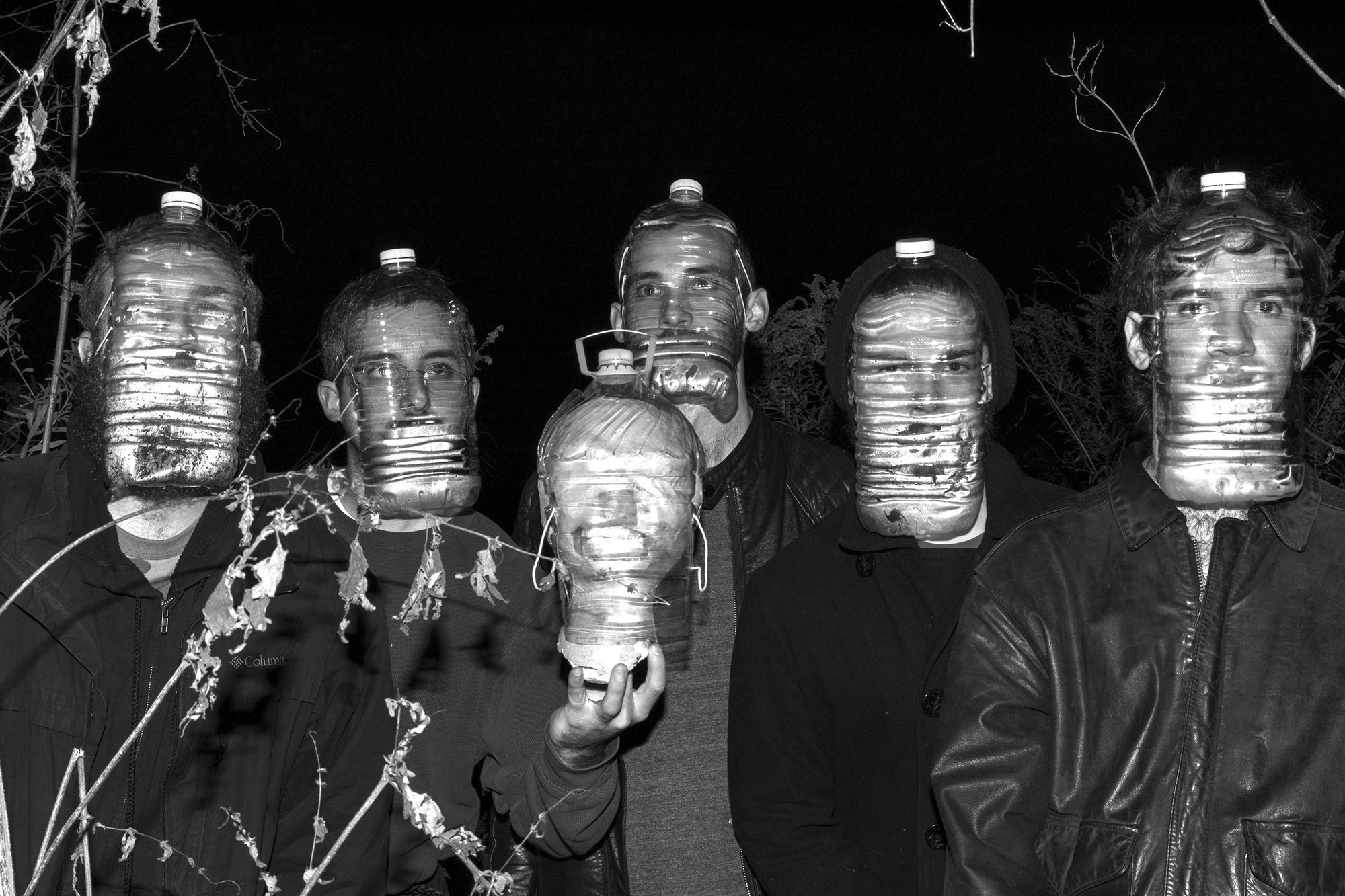 A black and white photo of 5 light-skinned people, Alex Brownstein-Carter, Eric Buller, Joe Ceponis, David Sigler, David Sabludowsky, whose faces are warped by gallon water bottles that they are wearing as masks tied around their heads. They are all wearing dark jackets and shirts. They are all staring straight ahead with their arms by their side except for the person second from the left who is holding up a mannequin head which also has a water bottle mask. The sky behind them is black and we can see some trees above and behind them. Photo by Sean Moore.