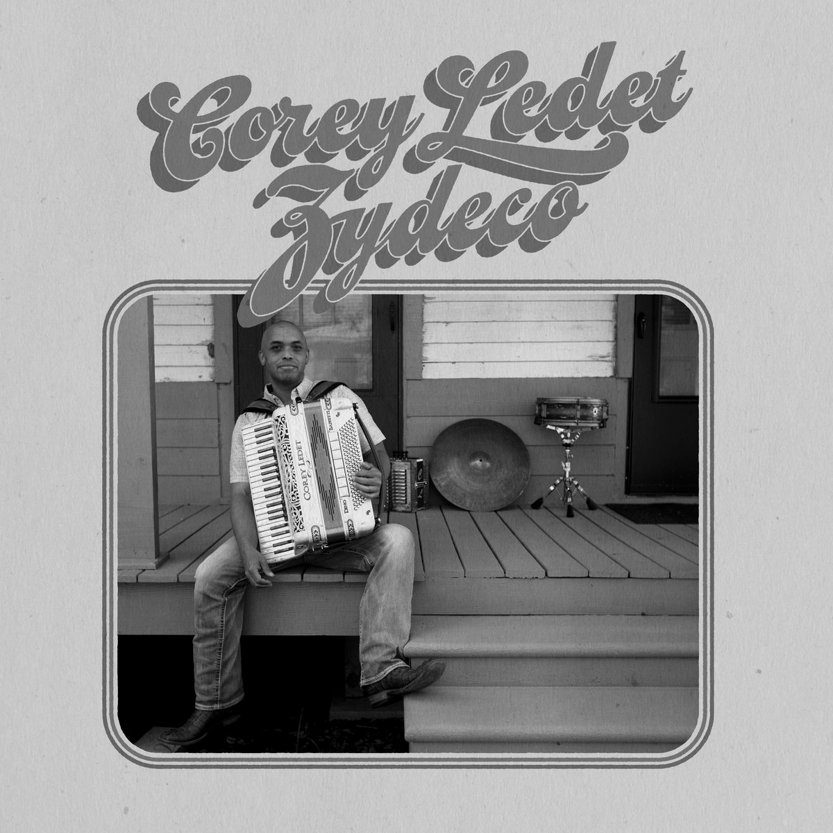 """Album cover for Corey Ledet Zydeco's self-titled album. It's a black and white photo of him sitting on a wooden porch with an accordion on his lap. He's dark-skinned and looking straight at the camera, and his foot is resting on one of the stairs. There are some drums and cymbals leaning up against the wooden panels of the building behind him. At the top reads """"Corey Ledet Zydeco"""" is a retro font."""