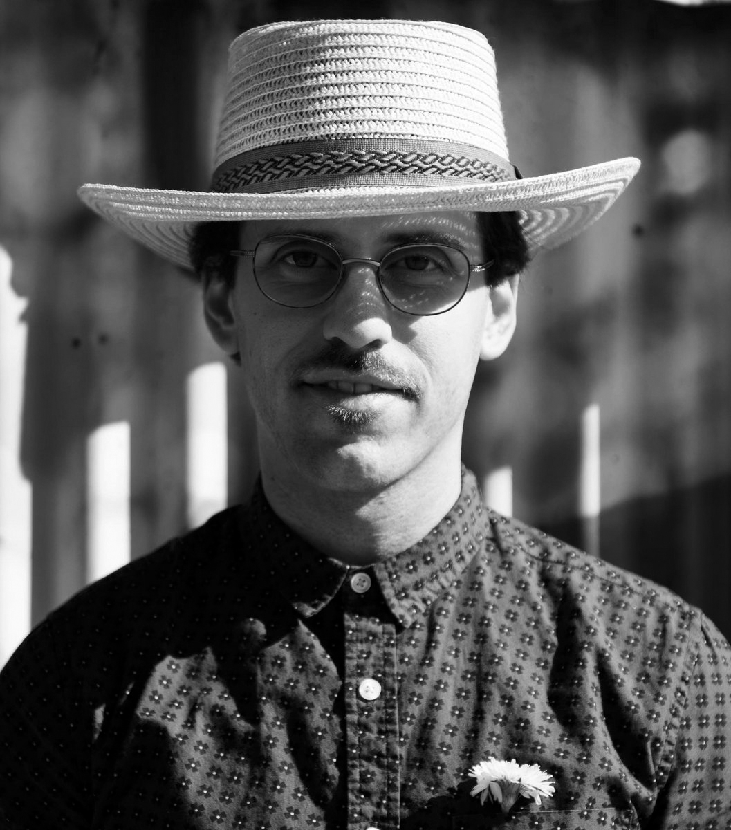 Album cover for The Shallow End of Denial by Jonathan Caplan. It's a black and white portrait of Jonathan Kaplan. He's light-skinned and has a goatee. He's wearing a patterned button-up shirt, a sun hat, and glasses.