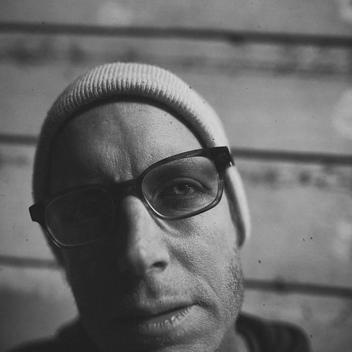 Album cover for New Confusion by R. Scully. It's a black and white photo of a close-up of R. Scully's face. He's light-skinned and is wearing a light beanie and glasses. The left half of his face is covered by shadow.