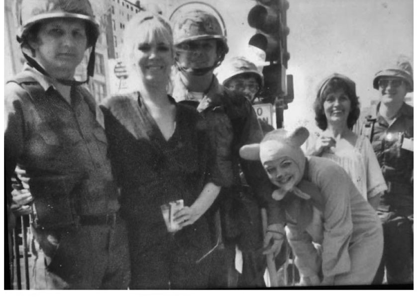 A black and white photo of several light-skinned people hanging out during Mardi Gras in 1979. A few people are wearing uniforms, either police or fire, that have helmets to go along with them. One person is dressed as a mouse and is bent over with their hands on their knees while they're smiling. There's a traffic light in the background.