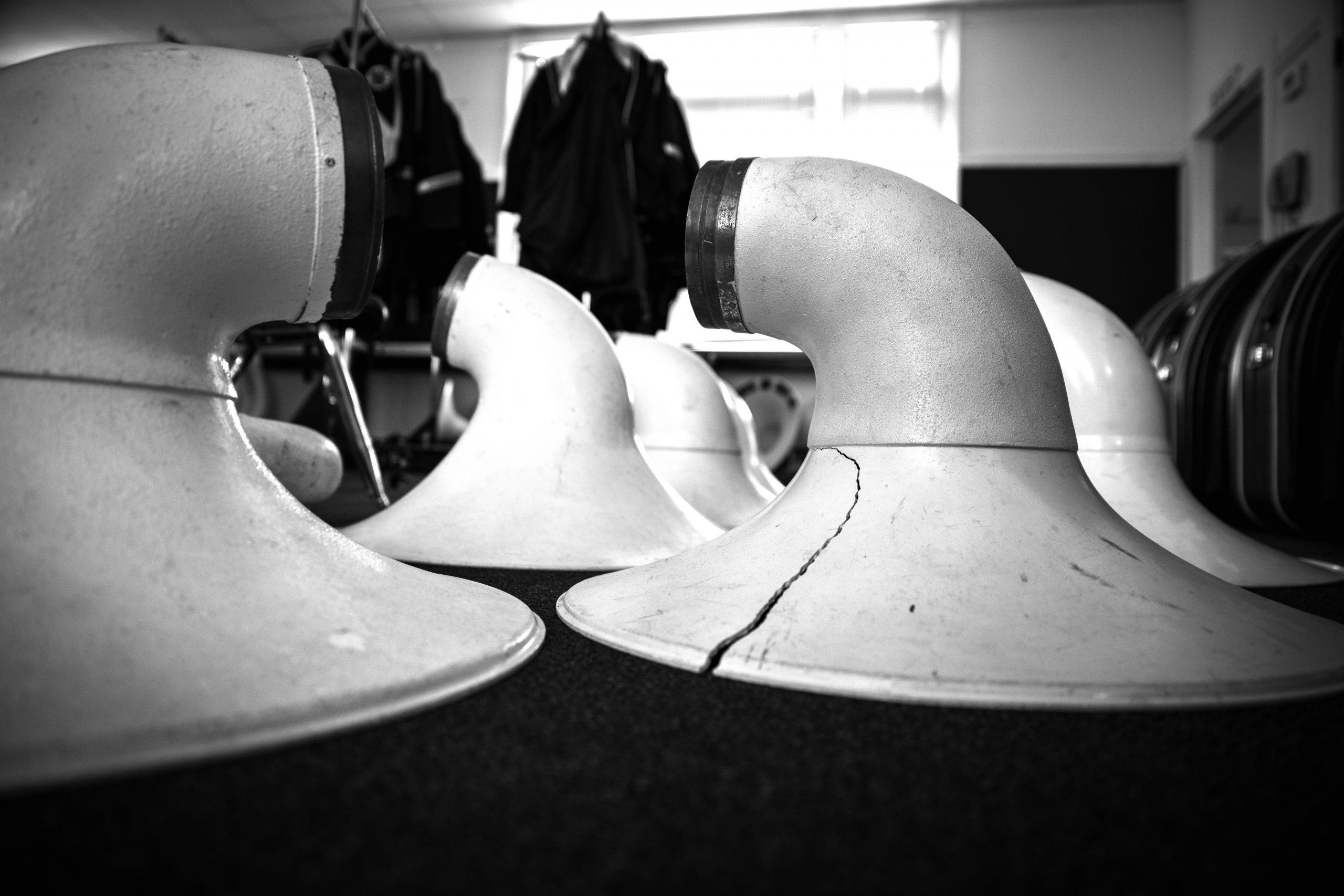 A black and white photo of the bells of tubas laying down on a table. The open, circular parts are laying face down, and they're all white. The bell most prominently in frame has a crack in it. There are chairs and instrument cases in the background. Photo by James Cullen.