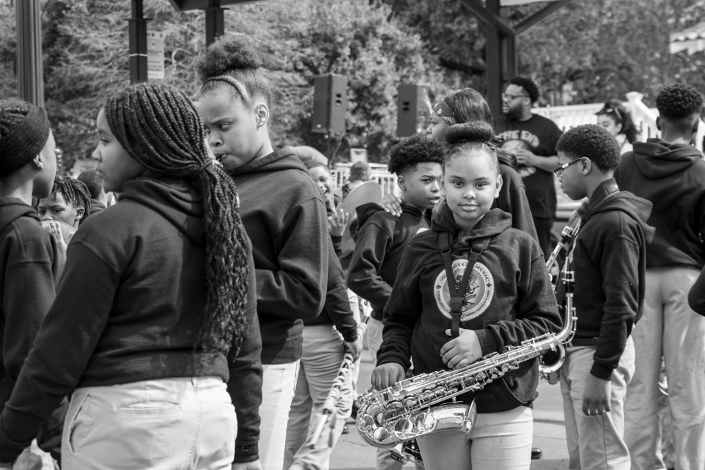 A black and white photo of a group of kids with their instruments in hand. They are all dark-skinned and are wearing matching sweatshirts and pants: the sweatshirts are black with a circular design in the middle, and their pants are khaki. One kid is looking directly at the camera and is in the center of the frame. Their hair is up in a bun, and their saxophone is around their neck. The rest of the kids are talking amongst themselves. There is an adult and some speakers visible in the background. Photo by James Cullen.