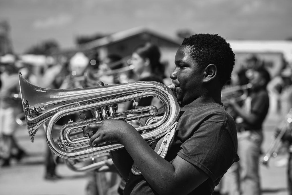 A black and white photo of a dark-skinned child playing a tuba at Jazzfest in 2018. They are facing the left of the frame, and their lips are pressed to the instrument. They have short hair and are wearing a dark t-shirt. In the background and out of focus are more kids playing instruments. Photo by James Cullen.