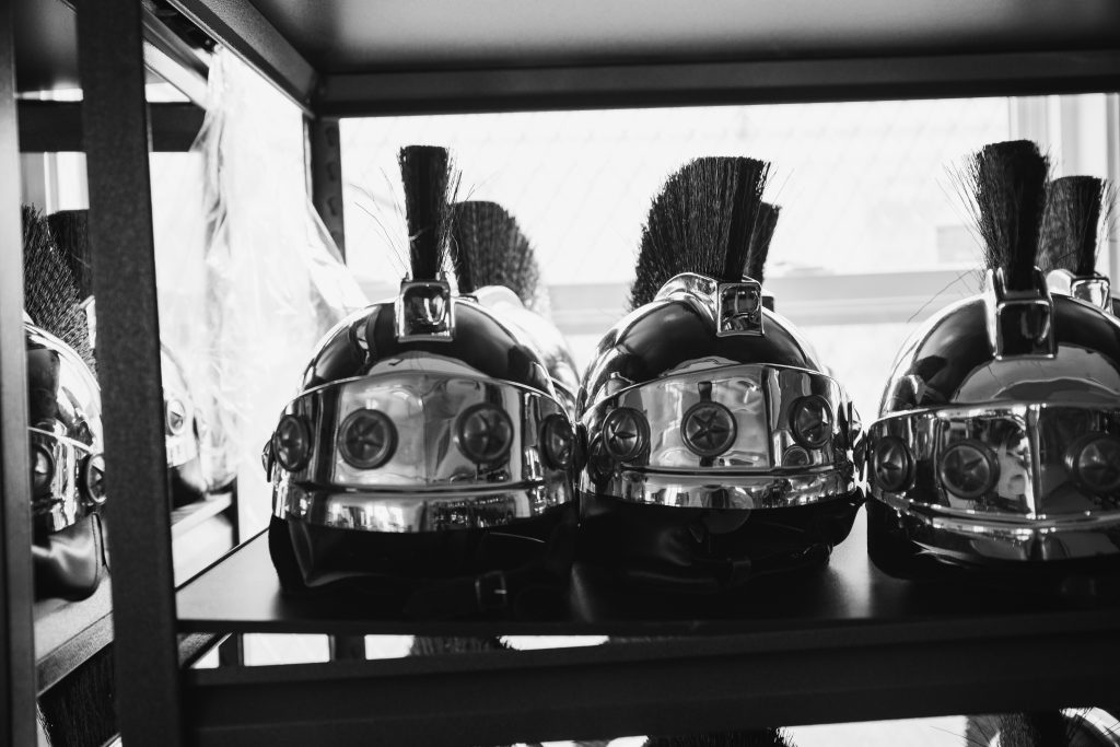 A black and white photo of a bunch of helmets that resembles Roman helmets. They are all sitting on a shelf in a case of some sort. They are shiny, and they have a line of a bristly material on the top. Photo by James Cullen.