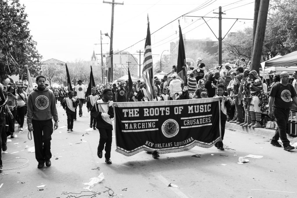 "A black and white photo of the Roots of Music marching band marching in the street during a parade in 2018. There are 2 dark-skinned kids holding up a banner in front of the rest of the band that reads ""The Roots of Music / Marching Crusaders / New Orleans Louisiana."" There's another line of kids behind them all holding flags, and then the band is behind that line. There are lots of people lined up on either side of the street for the parade. Photo by Adrienne Battistella."