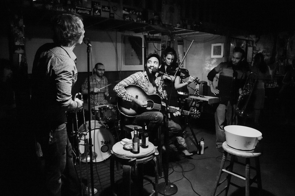 A black and white photo of Micah McKee sitting on a stool playing guitar at Saturn Bar. He's singing into the microphone and smiling, looking to one of his bandmates on the left. There are people in a semi-circle around him playing instruments, including trumpet, drums, and violin. There are 2 stools in front of the band, one with beer bottles on top and another with a bin. Photo by Josh Brasted.