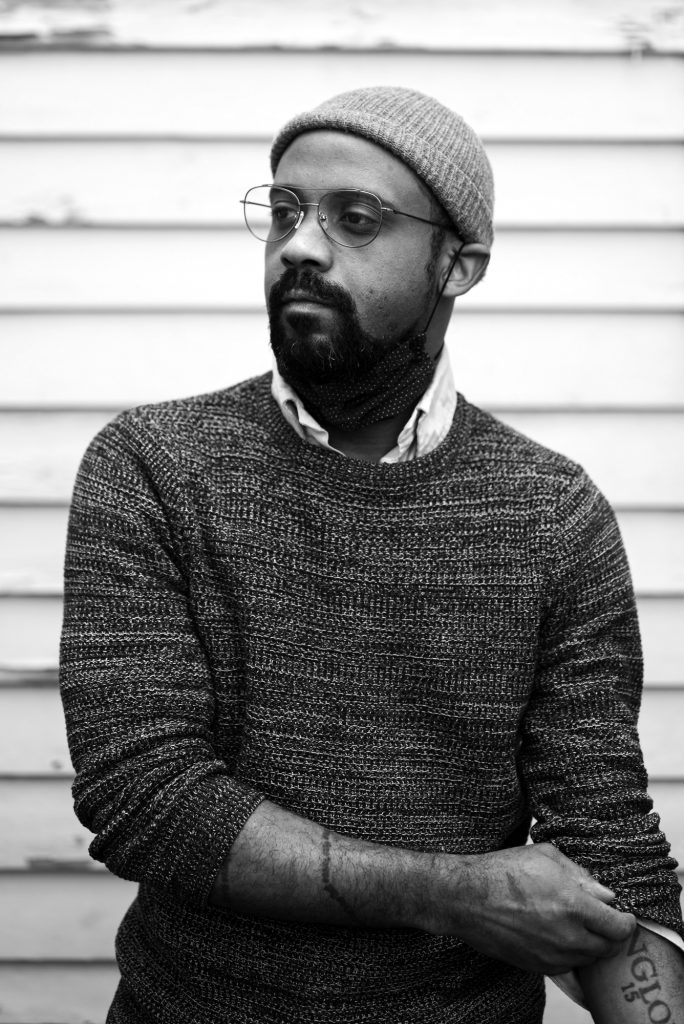 A black and white portrait of Micah McKee. He is dark-skinned and has a beard. He's wearing a sweater, a beanie, and glasses. He has a mask pulled down under his chin. He's looking to the left of the frame and is pulling up the sleeve of his sweater. Photo by Katie Sikora.