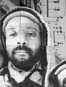 A black and white photo of Micah McKee's face that appears as though it's been stitched together from multiple photos. He's dark-skinned and has a beard. He's wearing a beanie and a hoodie pulled over it, and he's looking directly at the camera.