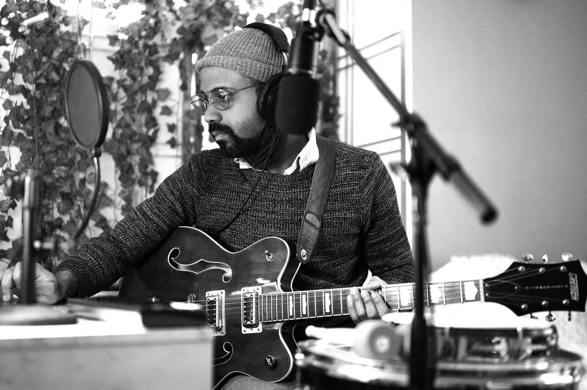 A black and white photo of Micah McKee sitting down at a desk with his guitar on his lap. He is dark-skinned and has a beard. He's wearing a sweater, a beanie, and glasses. He has noise-cancelling headphones on, and there is recording equipment around him. He's looking to the left of the frame, toward a screen out of frame. He's holding the guitar in his lap with his left hand, and his right hand is on the desk that his eyes are focused toward. There's a drum on the right that's out of focus, and there are plants in the background. Photo by Katie Sikora.