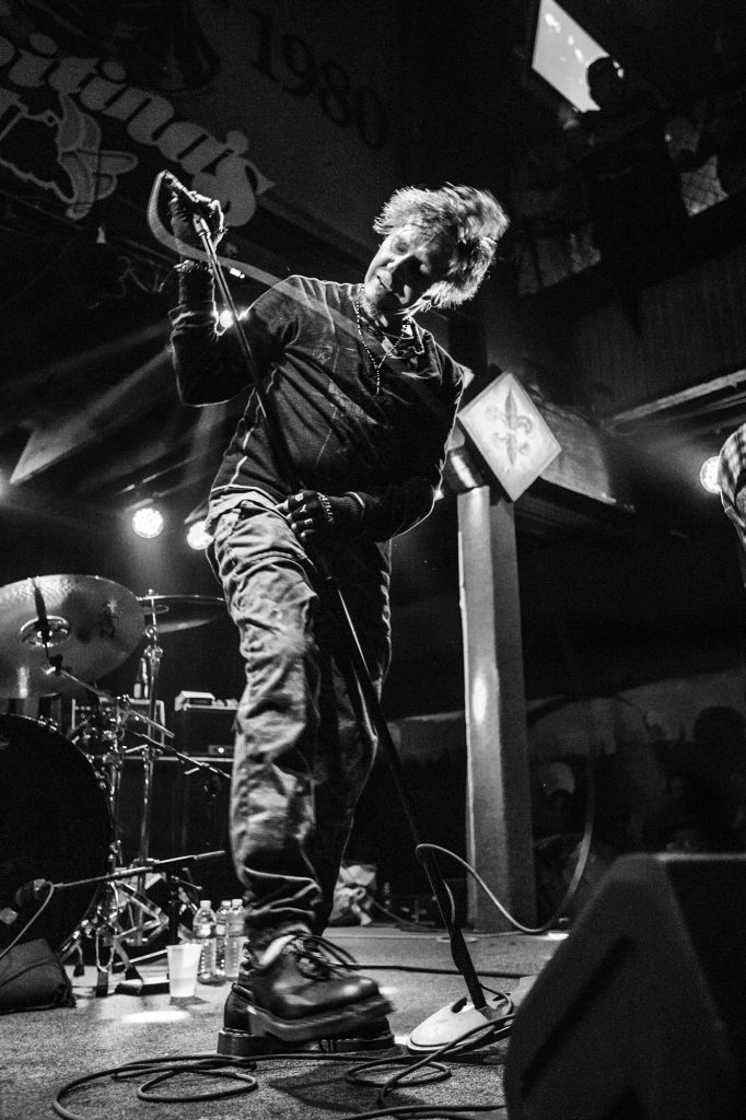 A black and white photo of Mike IX Williams performing at Tipitina's in 2018 for Eyehategod's 30th anniversary show. He's light-skinned and is looking down with his eyes closed. He's in the middle of moving, and the cord for the microphone in his hand is blurry with motion. He's wearing a dark, long-sleeved shirt, dark pants, and dark boots. There's a drum set behind him, and we can see part of the Tipitina's sign above. Photo by Adrienne Battistella.
