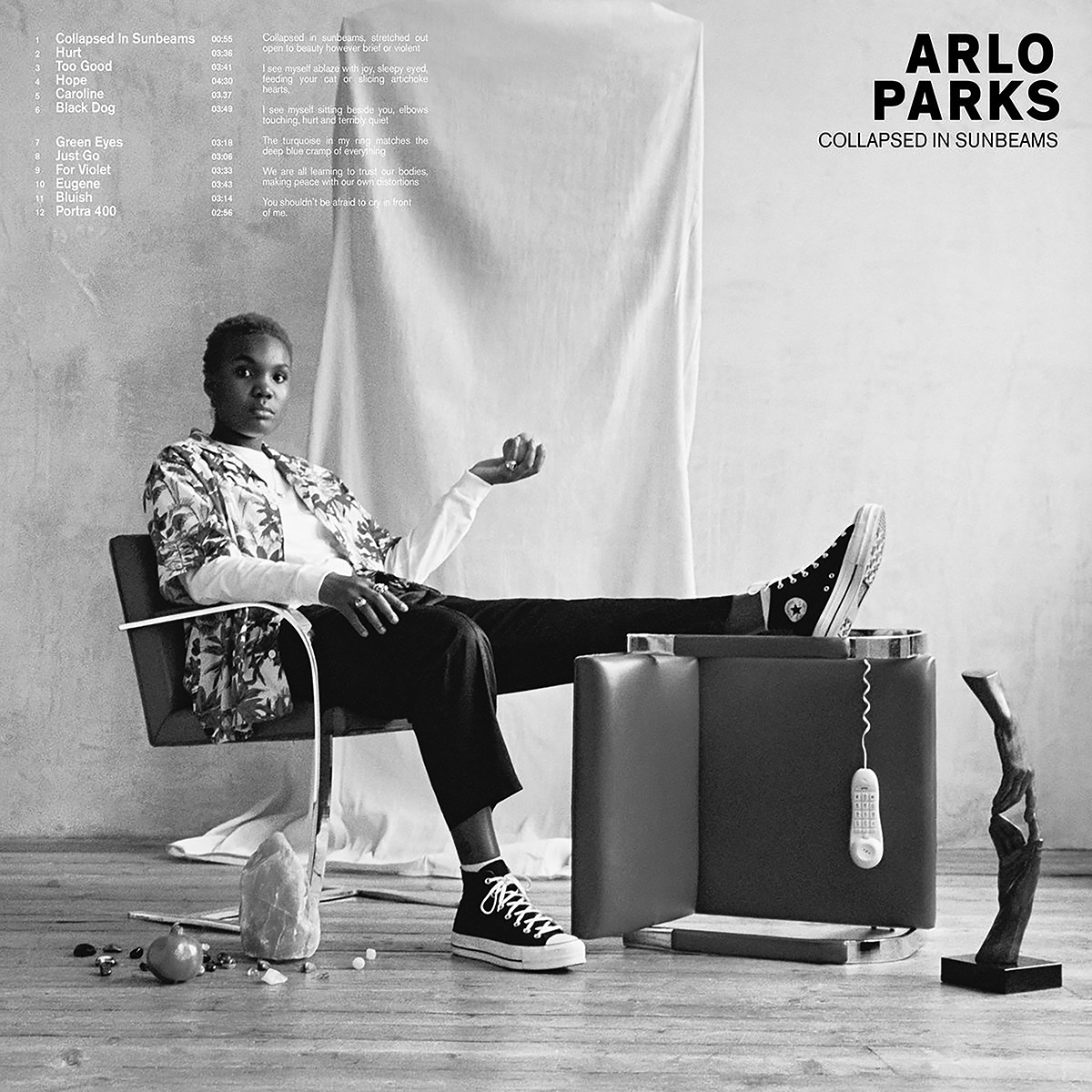 Album cover for Collapsed in Sunbeams by Arlo Parks. It's a black and white photo of Arlo Parks sitting in a chair with her foot up on a chair that's on its side. She's a Black woman with short hair. She's wearing a white long-sleeved shirt with an unbuttoned, short-sleeved floral shirt on top, as well as black pants and high top Converse. She's holding her left hand in the air and is looking directly at the camera. There are objects littered around the floor, like a salt lamp, a sculpture of 2 hands touching, and a remote hanging from the chair her foot is on.