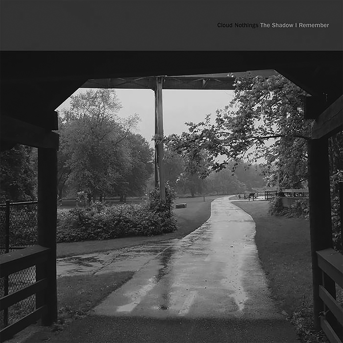 Album cover for The Shadow I Remember by Cloud Nothings. It's a black and white photo of a park. There's a covering and a sidewalk leading from under it, and the ground is wet. There are bushes and trees on either side.