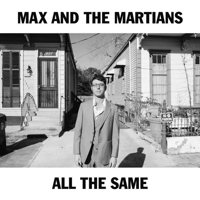 """Album cover for All the Same by Max and the Martians. It's a black and white photo of a person in a suit standing between 2 houses. Their eyes are closes, and they're smiling slightly. They're standing on the sidewalk, and the houses on either side of them are a little bit behind them. There's a strip of white space at the top and bottom. At the top reads """"Max and the Martians"""" and the bottom reads """"All the Same"""" in black letters."""