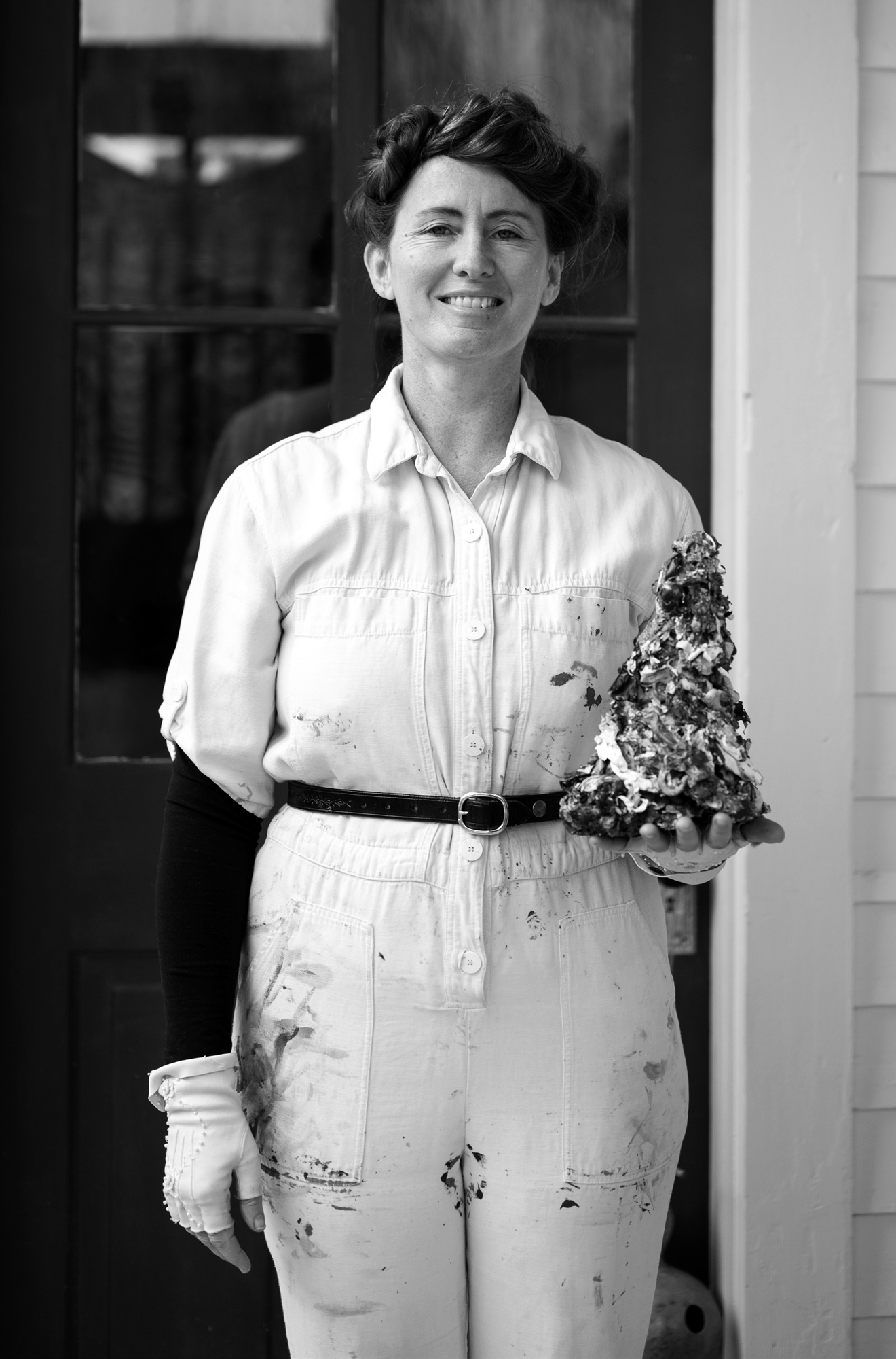 A black and white portrait of Rose McBurney standing and holding a sculpture. She's a light-skinned woman dressed in a light jumpsuit, and her dark hair is pulled back in a bun. She's smiling and is wearing white, fingerless gloves. Photo by Katie Sikora.