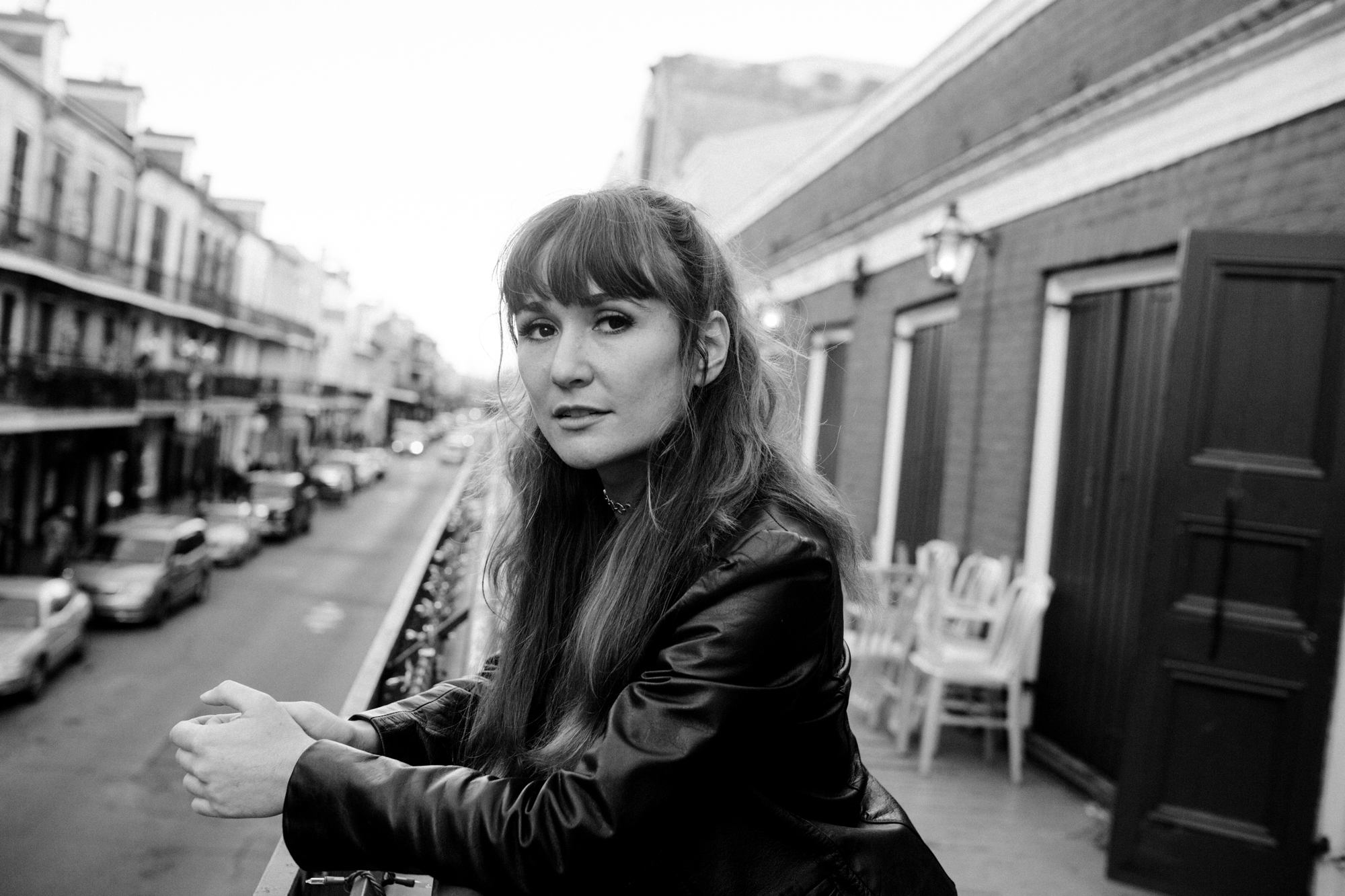 A black and white photo of Esther Rose leaning on a balcony and looking directly at the camera. She is light-skinned and has long hair that's halfway pulled up. She's wearing a leather jacket and a choker. We can see the French Quarter in the background, out of focus. Photo by Akasha Rabut.