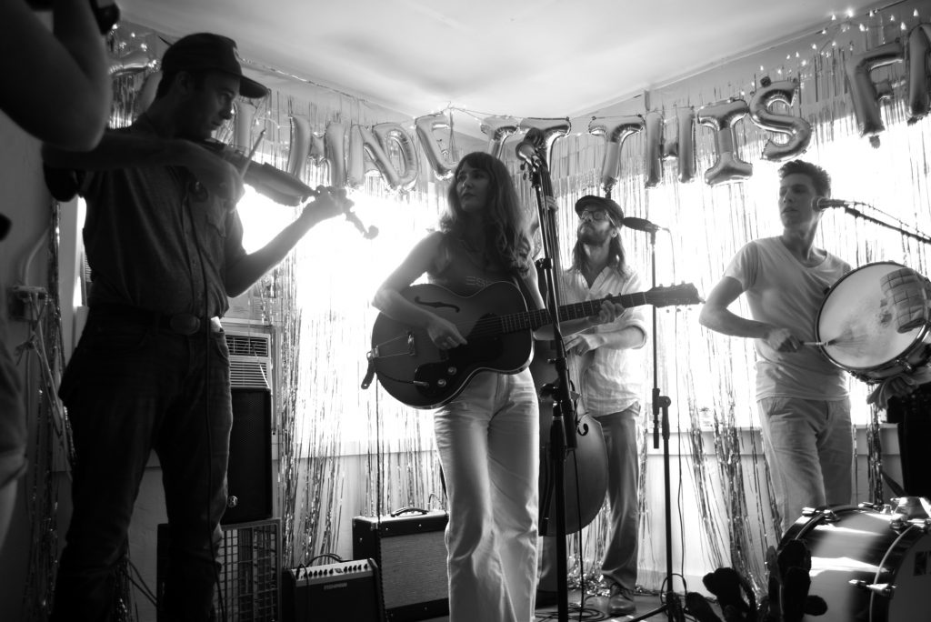 """A black and white photo of Esther Rose's release party for You Made it This Far at The White Roach in August 2019. On the left is Lyle Warner playing the violin; in the middle is Esther Rose playing guitar and singing; on her right is Dan Cutler playing the cello; on his right is Cameron Snyder playing a drum. Behind them are glittery streamers covering the windows and balloons that read """"You Made It This Far."""" Photo by Paris Achenbach."""
