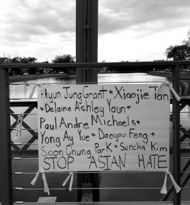 A black and white photo of a vigil at the Magnolia Bridge on Bayou St. John on Saturday, March 20 for the Asian American people murdered by a white supremacist on March 16. It's a white sign with the names of those whose lives were taken, and at the bottom reads Stop Asian Hate. Photo by Robin Bo Eun McDowell.