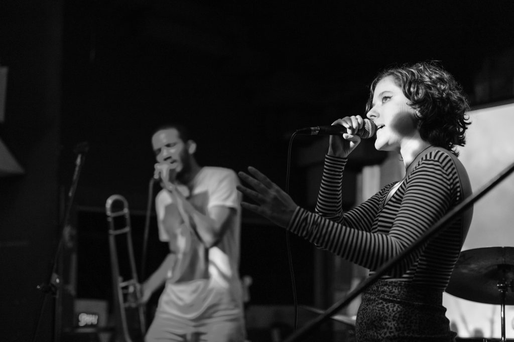 A black and white photo of People Museum performing at Gasa Gasa in 2018. Claire Givens is on the right and in focus; she's singing into a microphone and looking upward. She's light-skinned and is wearing a striped, long-sleeved shirt. Jeremy Phipps is on the left and out of focus. He's dark-skinned and holding a trombone in one hand and singing into a microphone with the other hand. Photo by Bryce Ell.