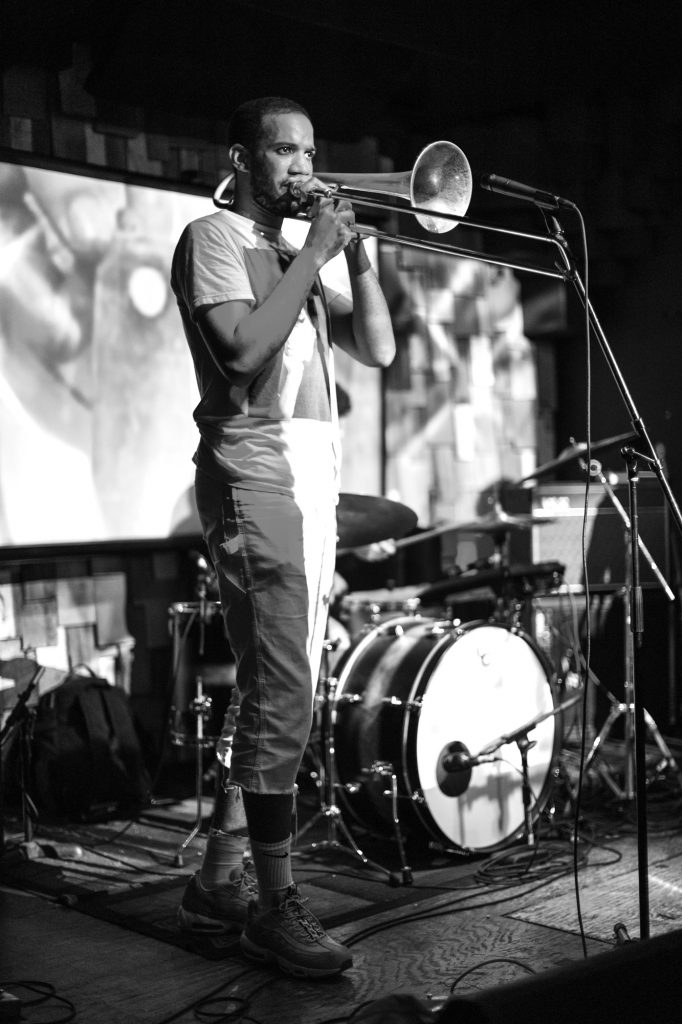 A black and white photo of Jeremy Phipps playing a trombone at Gasa Gasa in 2018. He is dark-skinned and is wearing a light t-shirt and light pants. There's a drum skit next to him and a screen with visuals projected onto it on the wall behind him. Photo by Bryce Ell.