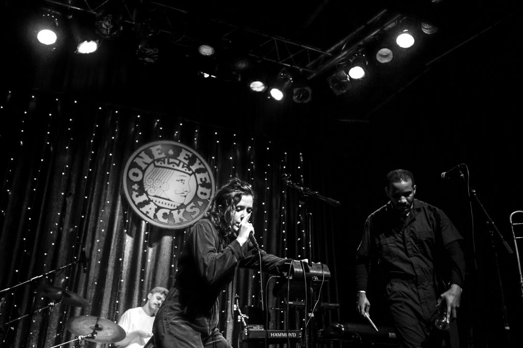"A black and white photo of People Museum performing at One Eyed Jacks in 2019. Claire Givens is on the left and is singing into a microphone. She's light-skinned and is wearing a dark jumpsuit. Jeremy Phipps is on the right with a drumstick in one hand and an instrument in the other. He's dark-skinned and is wearing a dark jumpsuit. There's a drummer behind them, and the ""One Eyed Jacks"" sign on the wall above the drummer. Photo by Katie Sikora."