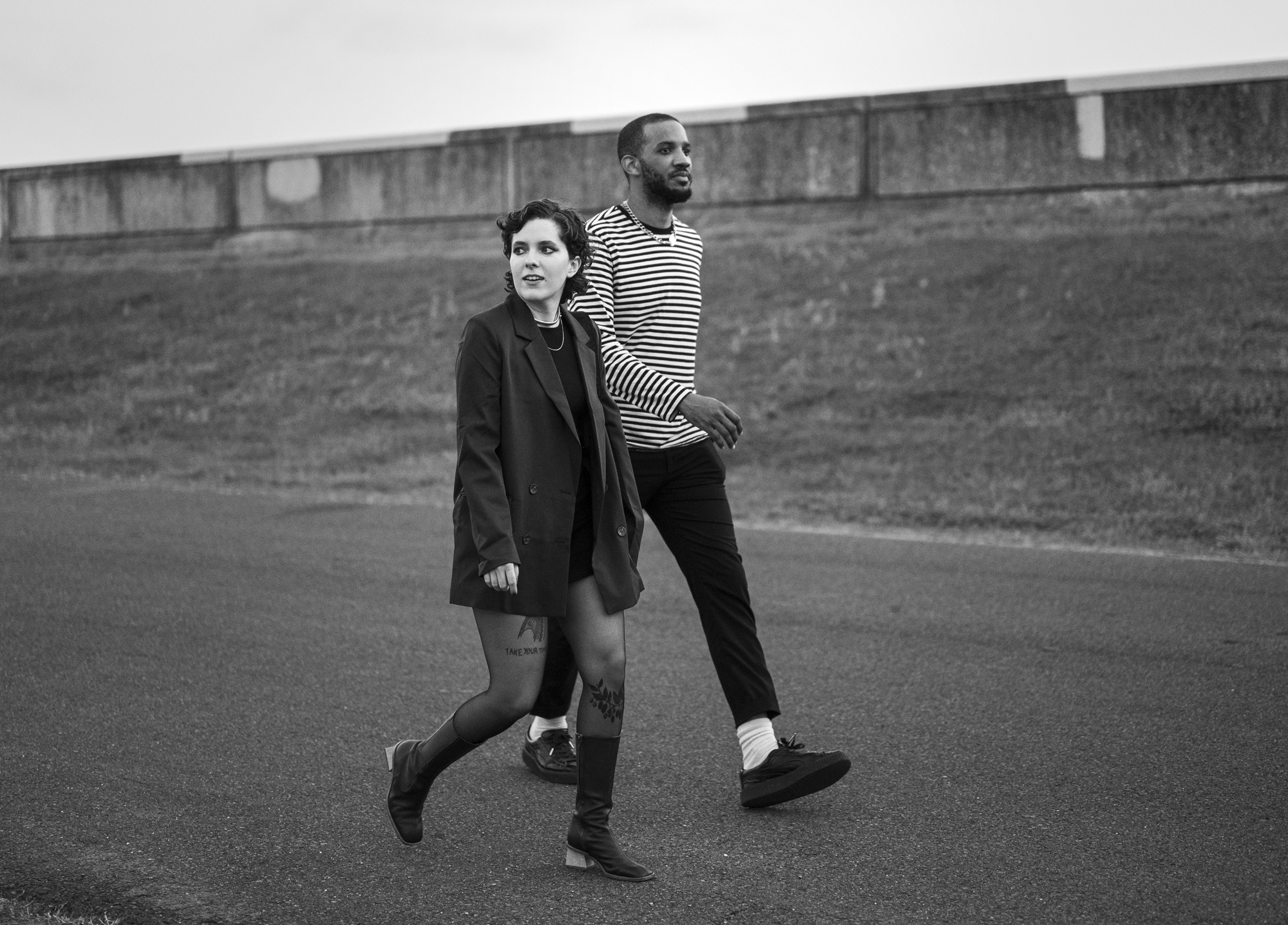 A black and white photo of Claire Givens and Jeremy Phipps, members of the band People Museum. They are walking next to each other and the levee is visible behind them. Claire is on the left; she's light-skinned and has dark brown hair. She's wearing a long black jackets, black tights, and long, dark boots, and there are tattoos on her legs visible through her tights. She's looking behind her. Jeremy is on the right; he's dark-skinned and has short hair and a beard. He's wearing a long-sleeved black and white striped shirt and black pants. He's looking ahead of him. Photo by Katie Sikora.
