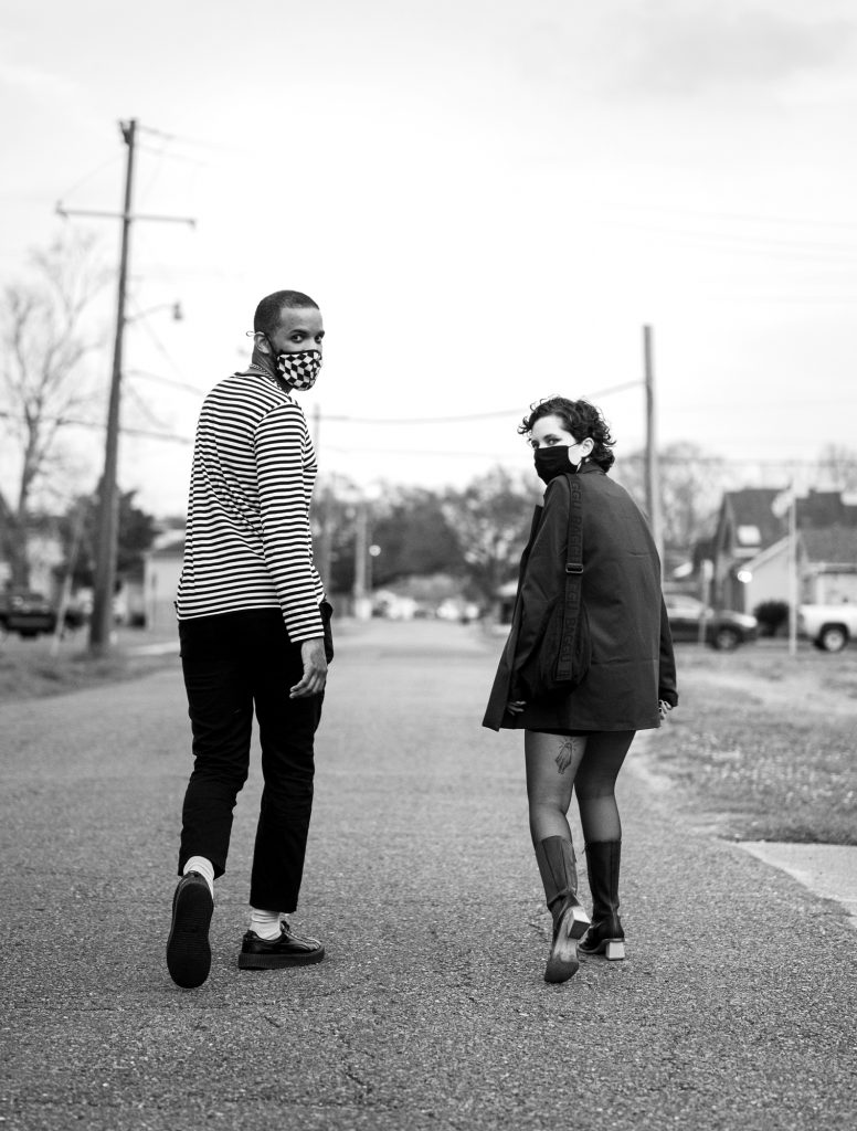 A black and white photo of Claire Givens and Jeremy Phipps, members of the band People Museum, walking away from the camera and looking behind them. Jeremy is on the left; he's dark-skinned and has short hair. He's wearing wearing a long-sleeved black and white striped shirt and black pants and a checkered mask. Claire is on the right; she's light-skinned and has dark brown hair. She's wearing a long black jackets, black tights, and long, dark boots, and a black mask. They're both looking over their shoulders, directly at the camera. Photo by Katie Sikora.