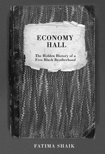 """Book cover for Economy Hall: The Hidden History of Free Black Brotherhood by Fatima Shaik. It's a grayscale picture of a notebook that has a texture like some sort of reptilian skin, and it reads """"Economy Hall / The Hidden History of Free Black Brotherhood."""" There's a dark gray border around the notebook, and at the bottom it reads """"Fatima Shaik."""