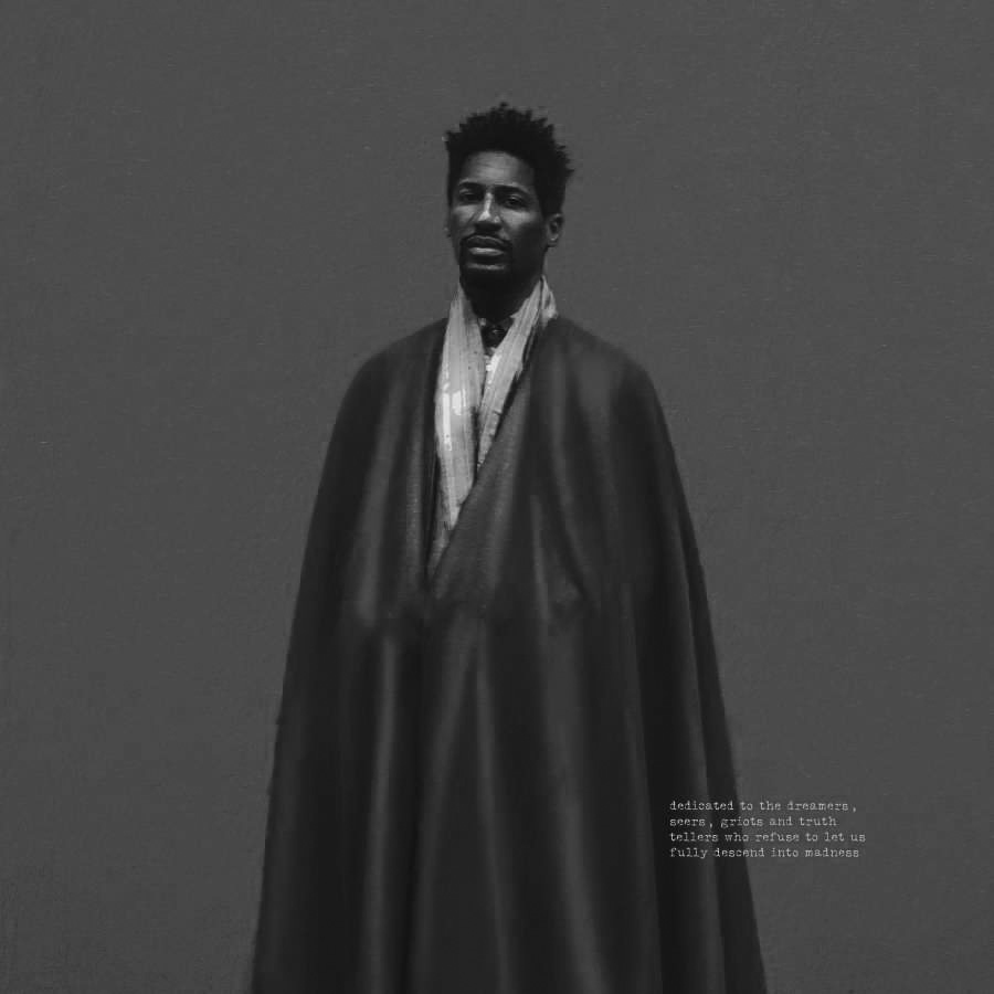 Album cover for We Are by Jon Batiste. It's a grayscale illustration of Jon Batiste wrapped in a cloak. He's dark-skinned and has short hair and a beard. He has a solemn expression and is looking straight forward. The background is solid and gray.