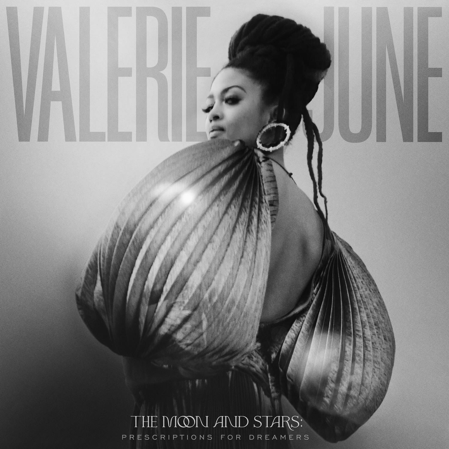 """Album cover for The Moon and the Stars: Prescriptions for Dreamers by Valerie June. It's a black and white photo of Valerie June in a dress with ballooning sleeves facing away from the camera and looking over her shoulder. She's dark-skinned and has her hair tied up on top of her head. She's wearing large hoop earrings and her gaze is cast downward, toward the camera. At the top reads """"Valerie June"""" in big letters, and in smaller letters at the bottom reads """"The Moon and the Stars: Prescriptions for Dreamers."""""""