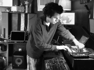 A black and white photo of Antoine Staib, a.k.a. TWANZ, handling his musical equipment. He's light-skinned and has dark hair, and he's looking down at his equipment while dealing with the notches on it. He's surrounded by speakers, computers, and other equipment.