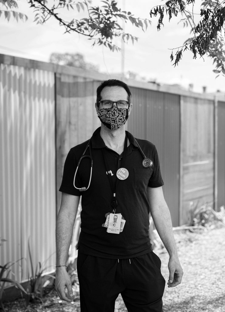 """A black and white photo of a light-skinned person in a dark Polo shirt and dark pants and a mask. He has a stethoscope around his neck, lots of badges and IDs on a lanyard, and a button that reads """"He Him."""" Above him are some leaves from branches overhead. Photo by Katie Sikora."""