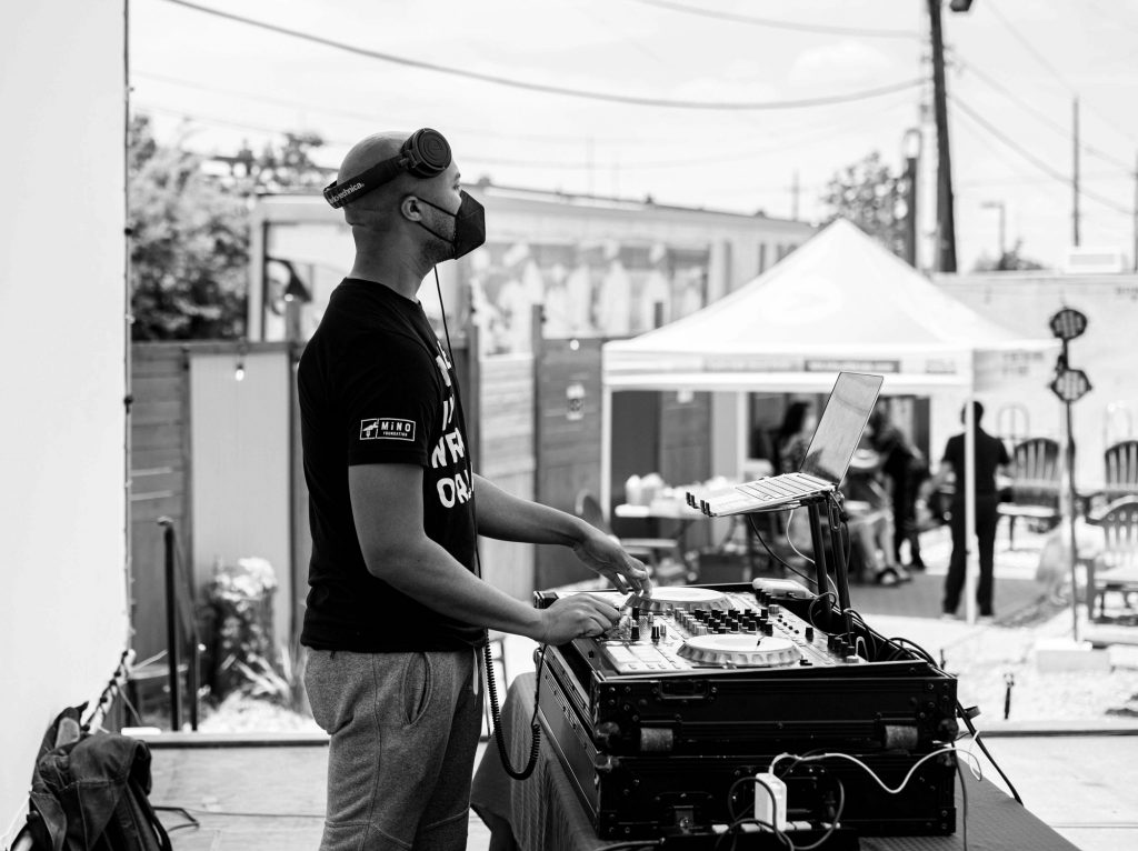 A black and white photo of DJ RQ Away performing at an event. He's dark-skinned and has headphones on the top of his head and a black mask. He's facing the right of the frame. In front of him is his DJ equipment and a laptop. In the background is a tent with people underneath it. Photo by Katie Sikora.