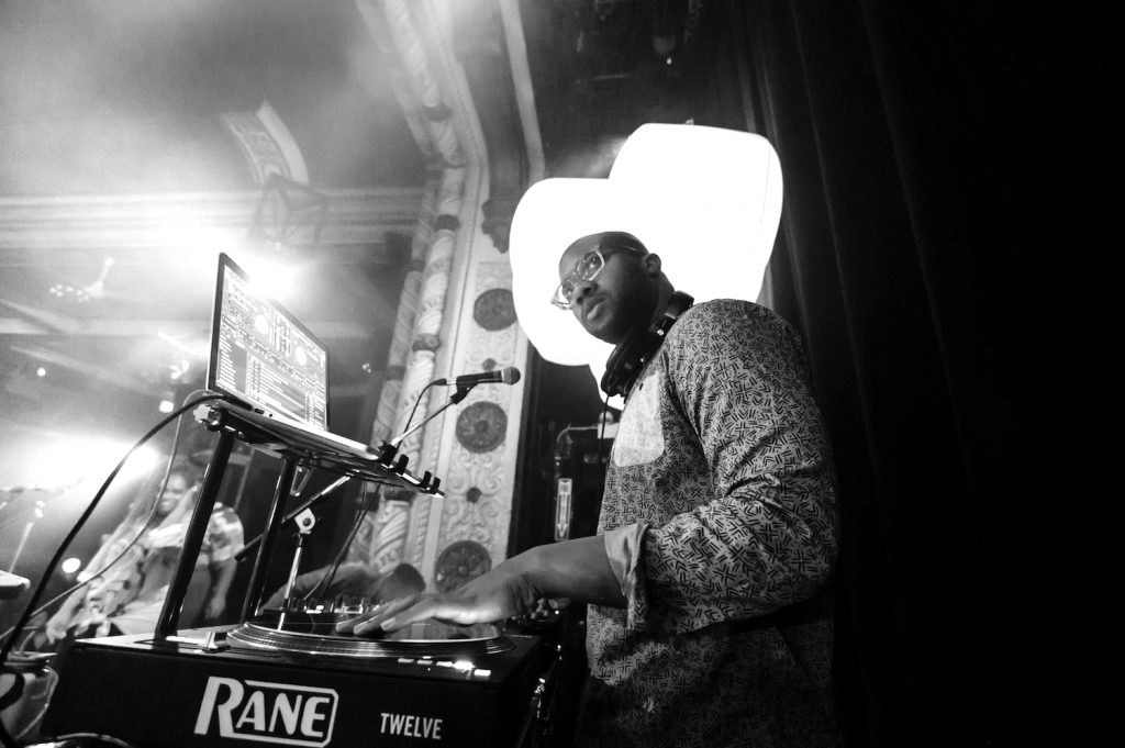 A black and white photo of DJ RQ Away performing in Chicago in 2019. He's dark-skinned and is wearing a patterned long-sleeved shirt. He's looking slightly above the camera, and the camera is positioned slightly below him. In front of him is his laptop and a turntable. In the background is a lamp of some sort. The architecture surrounding is sort of ornamental.