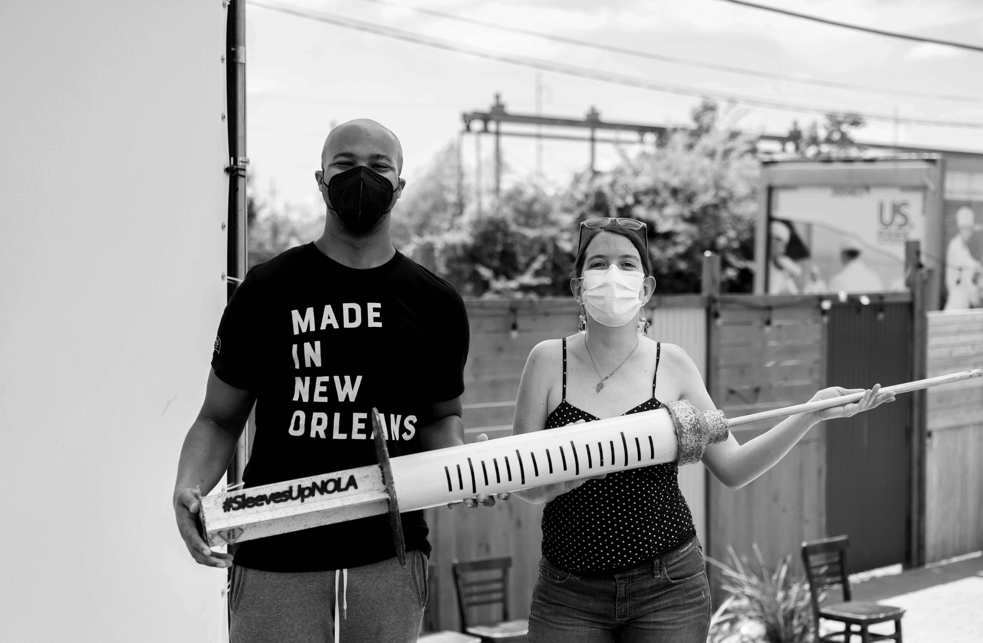 """A black and white photo of 2 people holding a giant, prop needle that reads """"#SleevesUpNOLA."""" The person on the left is dark-skinned and bald, and they're wearing a black mask and a black shirt that reads """"Made in New Orleans."""" The person on the right is light-skinned and is wearing a polka-dotted tank top and jeans and a white mask. Their hair is pulled back and they have sunglasses on the top of their head. Photo by Katie Sikora."""