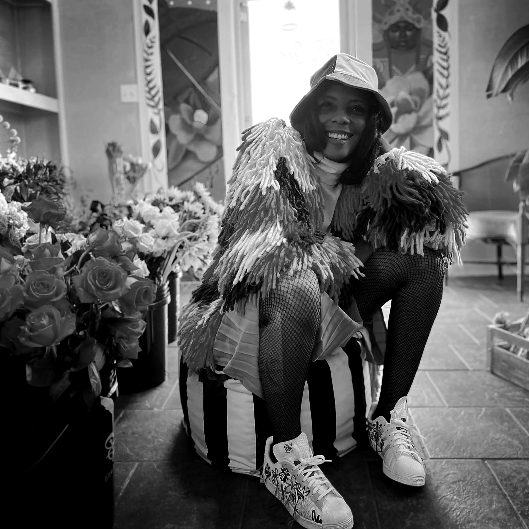 A black and white photo of Brandi Charlot sitting, in costume, surrounded by flowers. She is a Black woman and she's wearing a bucket hat, fishnets, and a jacket with lots of differently colored tassels. She's smiling widely and is looking slightly above the camera. Around her are many different bouquets of flowers. Photo courtesy of Brandi Charlot.