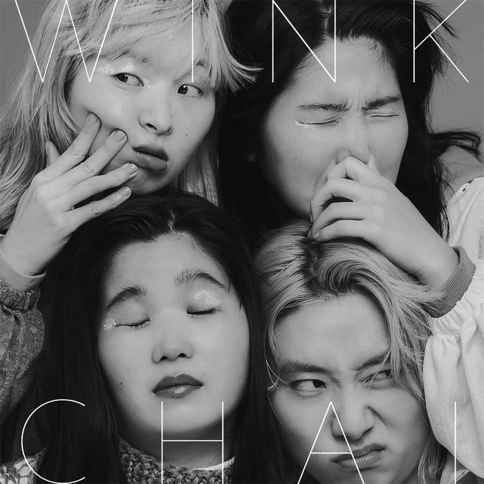 Album cover for Wink by CHAI. It's a black and white photo of 4 Japanese women with their heads close together. The woman in the top left has blond hair and her hand is touching her face while she's looking left. The woman in the top right has dark hair and is holding her nose and her eyes are closed tightly. The woman in the bottom left has dark hair and is closing her eyes and looking exasperated. The woman in the bottom right has blond hair and is making a sour face while the woman above her rests her arm on her face.