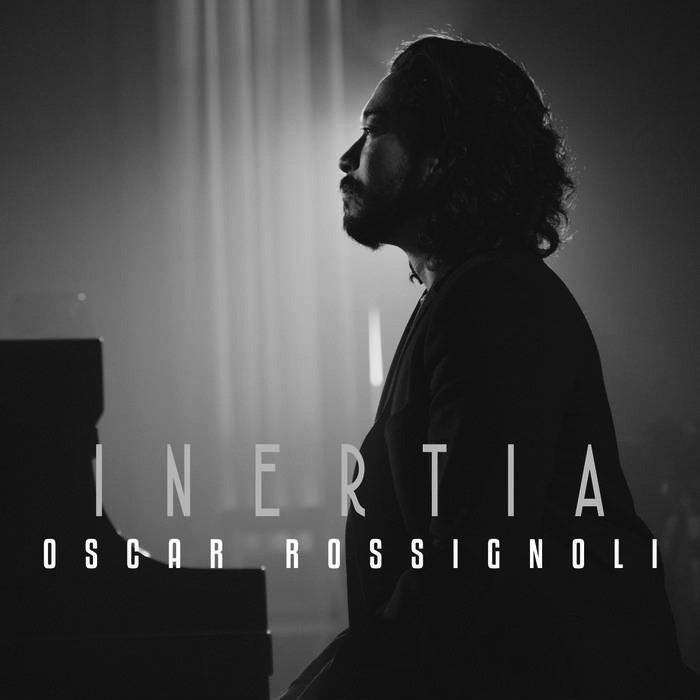 """Album cover for Inertia by Oscar Rossignoli. It's a black and white photo of Oscar Rossignoli sitting at a piano. It's a backlit picture, and he's wearing a dark suit and looking to the left of the frame. Near the bottom reads """"Inertia Oscar Rossignoli."""