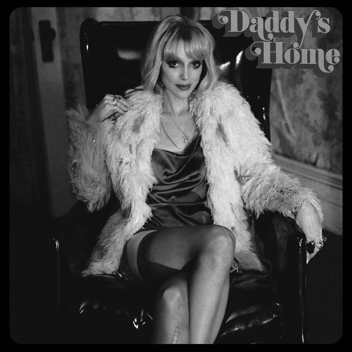 """Album cover for Daddy's Home by St. Vincent. It's a black and white photo of St. Vincent dressed in a silk dress and fur coat sitting in a chair. She's light-skinned and has blond hair. She has her legs crossed and is looking directly at the camera seductively. At the top right reads """"Daddy's Home"""" in a retro font."""