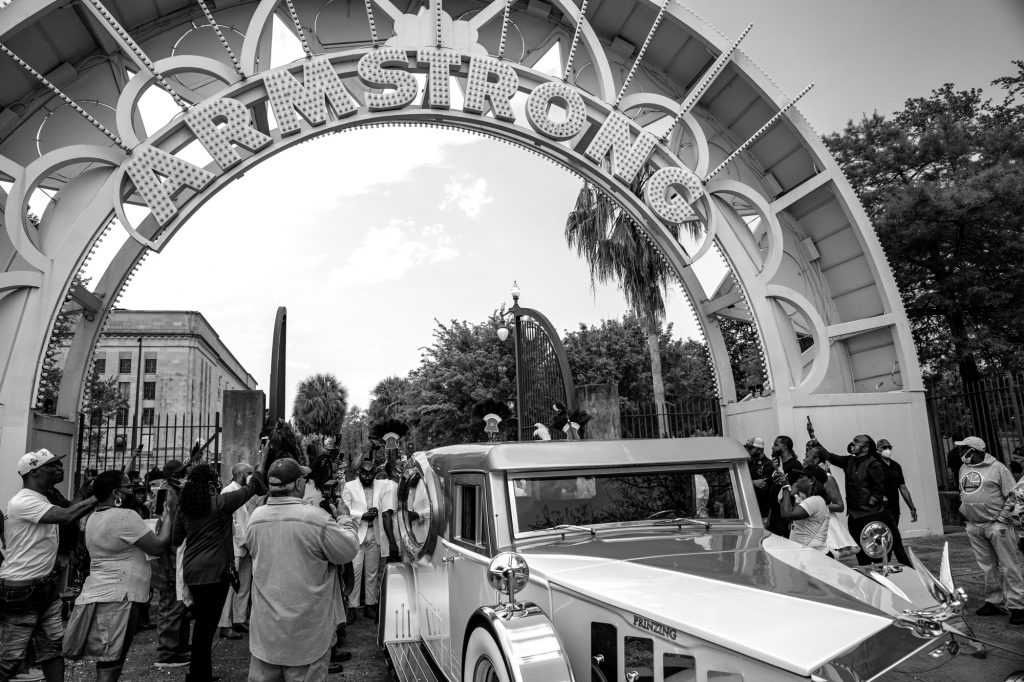 A black and white photo of a funeral procession for Keelian Boyd Sr., Big Chief Dump of the Young Maasai Hunters. There's a sleek car exiting the arches of Armstrong Park, and everyone surrounding the car is looking behind it and holding their phones and cameras up to take pictures. Photo by James Cullen.