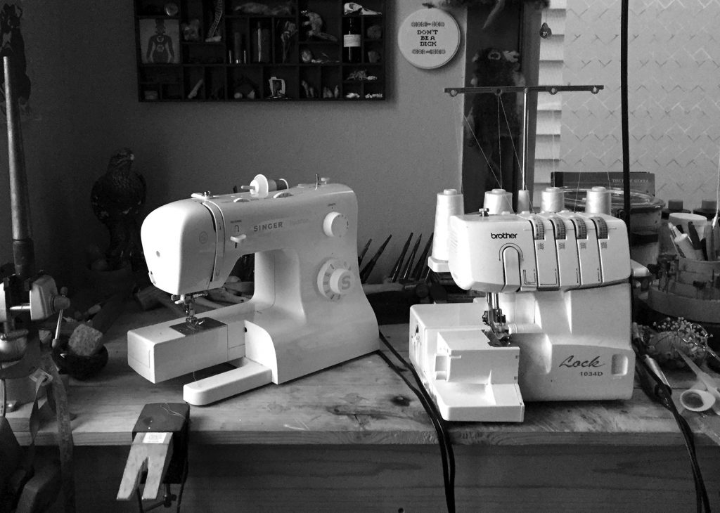 A black and white photo of 2 sewing machines next to each other on top of a table with lots of other supplies. Photo courtesy of Aubrey Edwards.