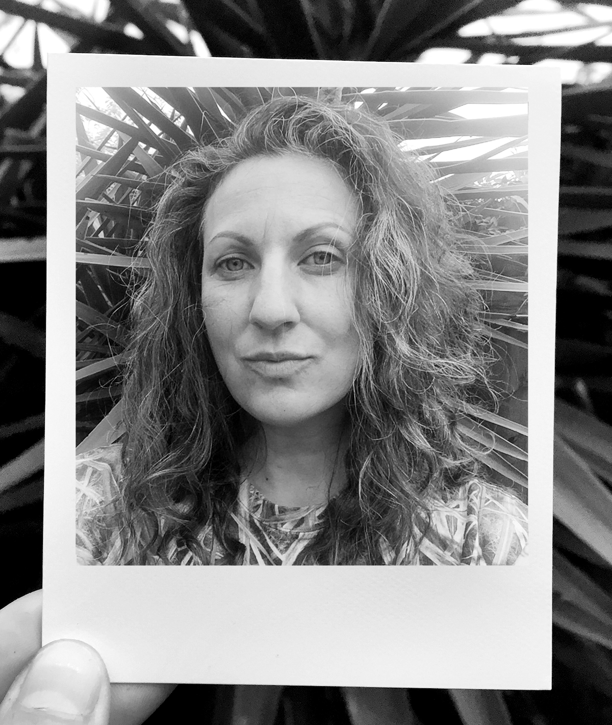 A black and white photo of someone holding a polaroid portrait photo of Aubrey Edwards. She is light-skinned and has long, curly hair, and there's a plant behind her. We can see the tip of someone's thumb and finger holding the polaroid. Photo courtesy of Aubrey Edwards.