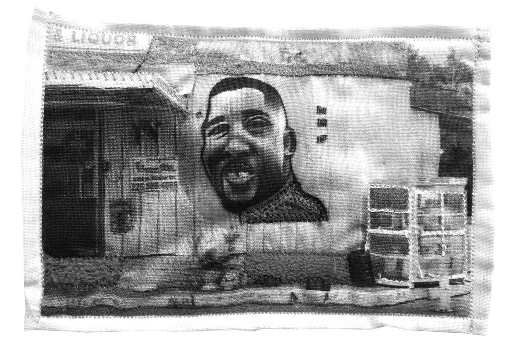 """A black and white photo of a mixed media/textile work by Aubrey Edwards of Alton Sterling's face painted on the side of a building titled """"Murder of Alton Sterling, Baton Rouge, LA 2016."""" In the painting he is smiling, and we can see a sign above and to the left that reads """"& Liquor"""" with the first part of the sign cut off."""